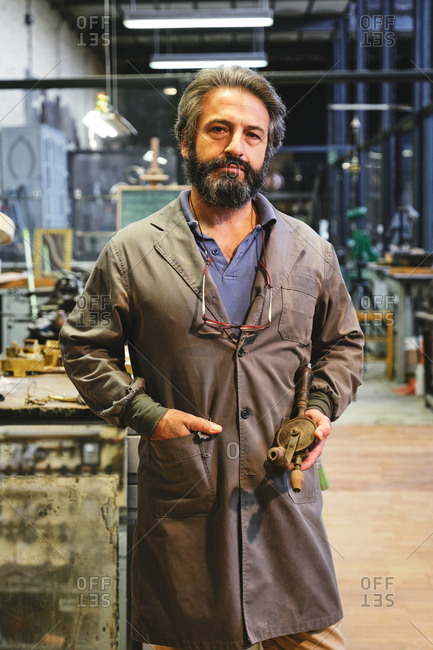 Confident middle aged bearded ethnic jeweler in robe with hanging eyeglasses standing with hand in pocket and looking at camera while holding handmade golden object in studio