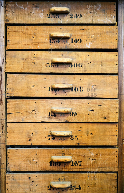 Archive representing identical light brown wooden drawers with rectangular handles and numbers on uneven surface with spots and words in workshop