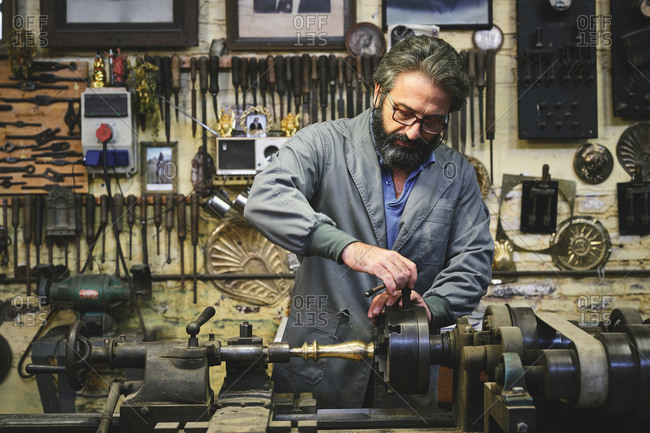 Focused mature bearded goldsmith in eyewear working on polishing machine in workshop while holding pointed metal stick