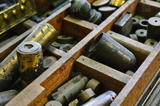 From above of old golden cylinders with spots on surface near various rounded metal rolls in wooden drawer with sections in studio