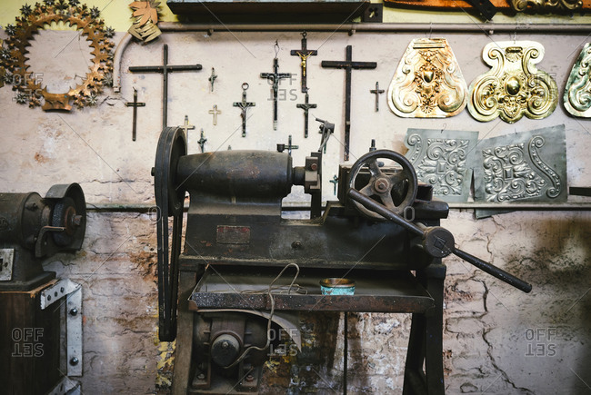 Aged metal rolling mill machine with steering wheel near shabby wall with collection of crosses and ornamental golden items in studio