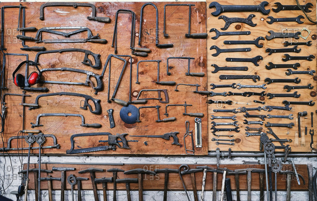Set of different saw frames with headset near various nut wrenches above metal hammers with wooden handle on brown board in studio