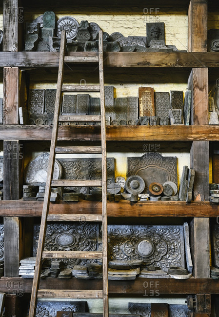 Wooden shelves with various metal decorations and ladder arranged in grungy goldsmith workshop