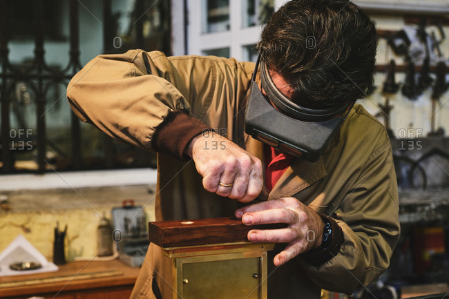 Focused mature goldsmith in head magnifying glasses and uniform working with rectangular engraving in gold frame in workshop near wall with professional tools