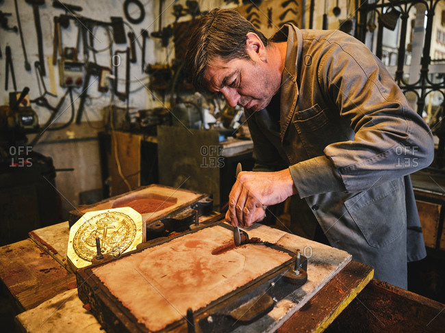 Focused professional mature craftsman cutting sand mold while working with metal casting in craft goldsmith workshop