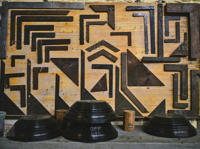 Set of metal corners of various sizes arranged on wooden board near professional tools in goldsmith workshop