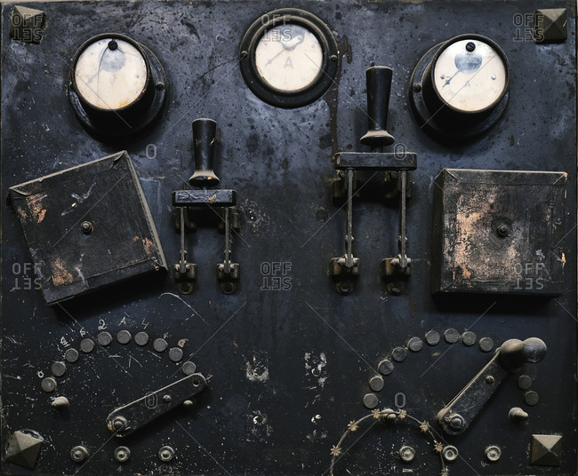 Aged metal control panel with switches and analogue gauges in craft workshop