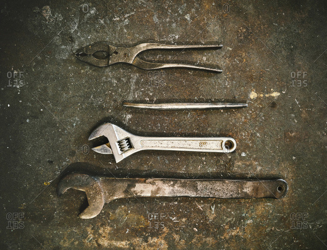 Top view set of various metal instruments for metalworking including wrenches and pliers arranged on grunge gray surface