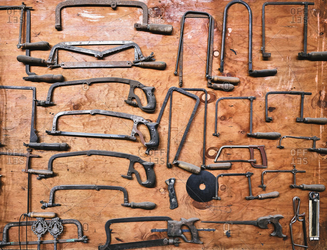 Top view of various aged metal hacksaws for craft work arranged on weathered wooden surface in workshop