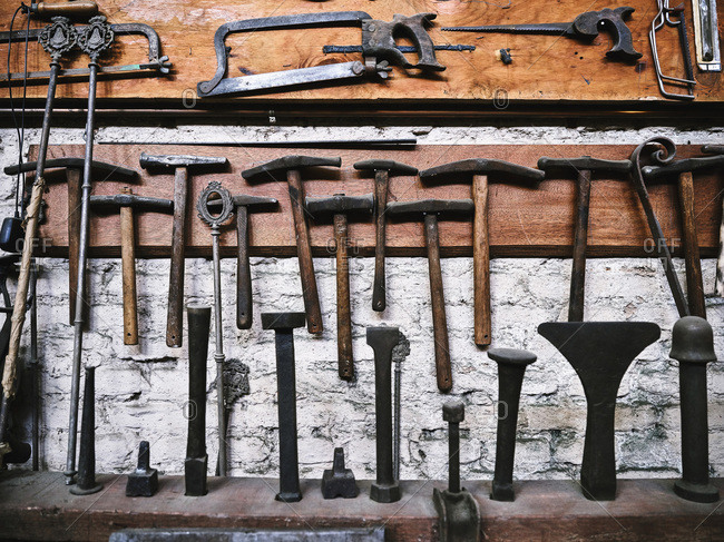 Front view of various ages hacksaws and hammers for craft work arranged on weathered wooden surface in workshop