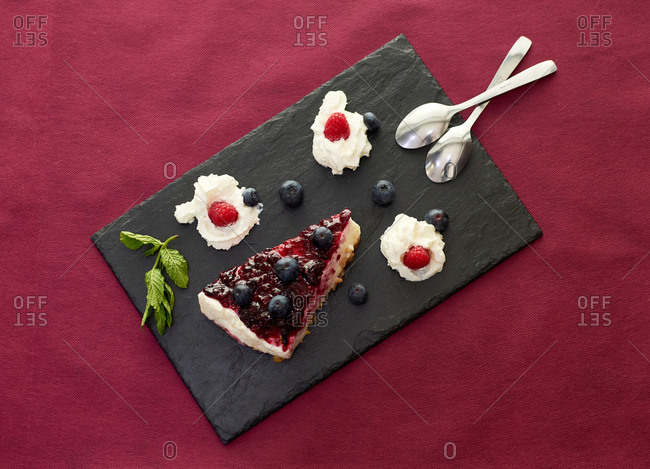 Top view of tasty cheesecake with berries and whipped cream served on slate board on table in luxury restaurant
