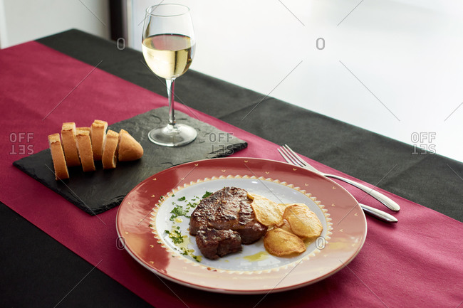 Palatable beef steak and potato chips on plate arranged on table with glass of white wine and baguette on slate board in expensive restaurant
