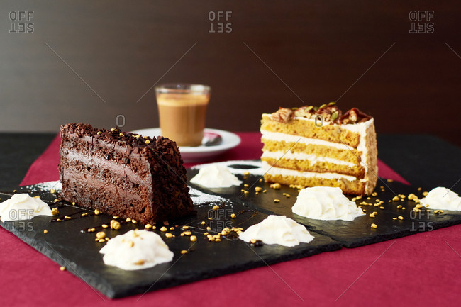 Glass cup of hot latte with coffee beans placed on table near pieces of cakes