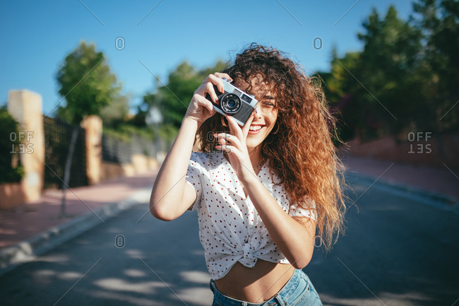 Content female in casual wear and eyeglasses taking photo on digital camera in sunlight outdoors
