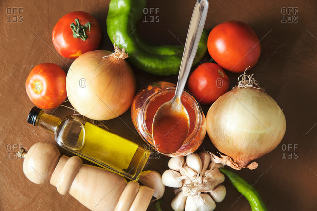 Top view composition with tomato sauce in jar placed amidst fresh vegetables and olive oil with spices prepared for cooking Bolognese sauce