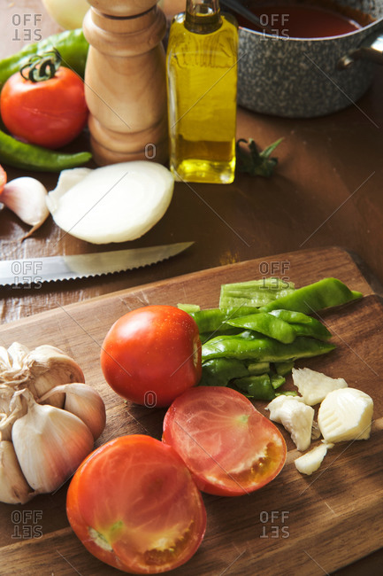 Chopped green pepper with garlic and tomatoes on cutting board placed on table with ingredients during preparation of Bolognese sauce