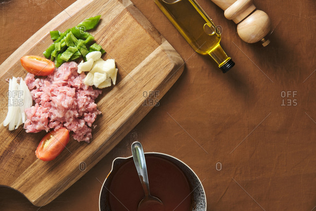 Top view of raw noodles in bowl placed on table near cutting board with minced meat and chopped vegetables during preparation of traditional Italian Bolognese pasta