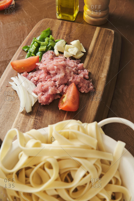 Raw noodles in bowl placed on table near cutting board with minced meat and chopped vegetables during preparation of traditional Italian Bolognese pasta