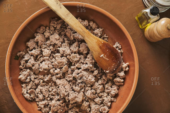 Top view closeup of minced meat in frying pan with wooden spoon during process of cooking Bolognese sauce