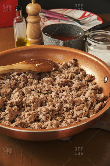 Minced meat in frying pan with wooden spoon during process of cooking Bolognese sauce