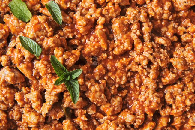 Closeup top view of appetizing homemade pasta with Bolognese sauce served with fresh basil leaves