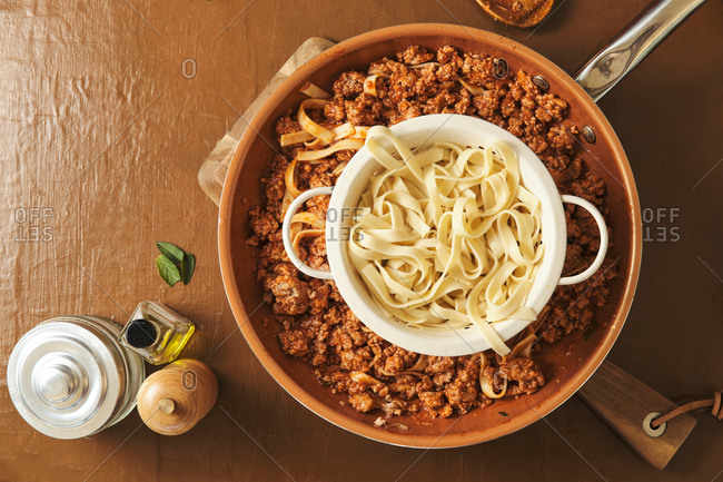 Top view of bowl with boiled noodles placed over frying pan with Bolognese sauce during cooking delicious pasta in kitchen