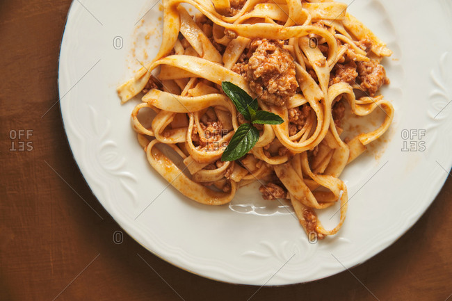Top view of appetizing homemade pasta with Bolognese sauce served with fresh basil leaves on white plate