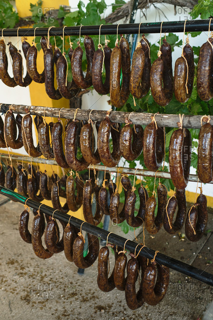 Selection of fresh homemade traditional Spanish chorizo sausages hanging on rack outside of local factory