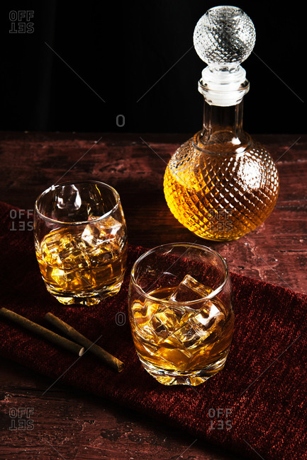 Close-up of two glass of whiskey on a table and a bottle of whiskey