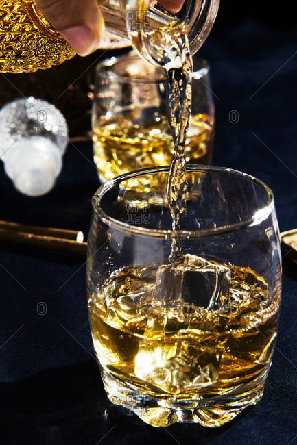 Anonymous person serving whiskey in a glass