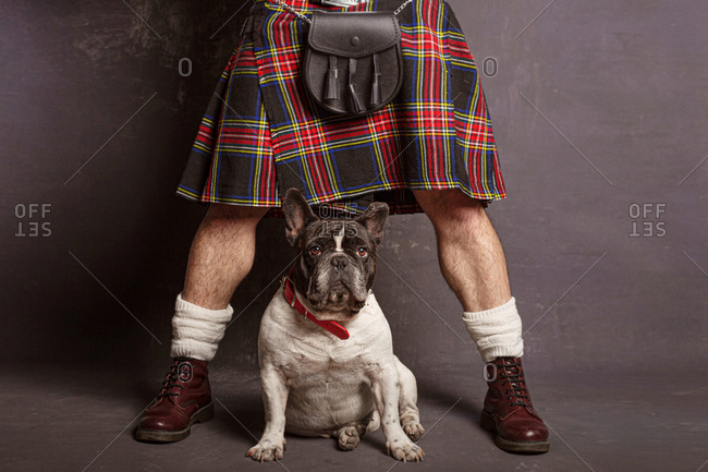 Crop anonymous man in Scottish skirt and leather boots with leather shoulder bag standing with legs apart near cute French Bulldog in red collar