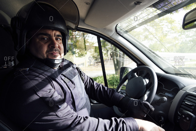 Side view of serious plump middle aged police officer in uniform and protective helmet driving automobile in countryside at work while looking at camera