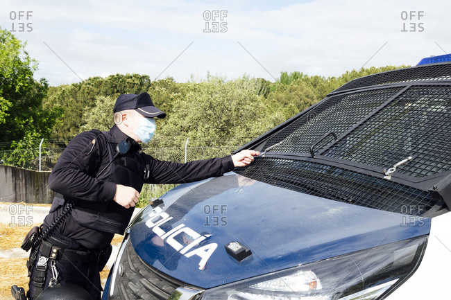 Side view of anonymous police officer in sterile mask and uniform with automatic firearm touching windshields on company car during quarantine period at work in countryside under cloudy sky