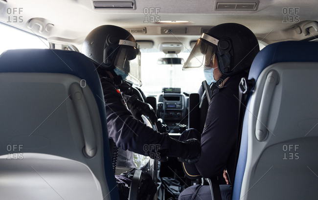 Policemen in medical mask and protective gear talking on radio set while sitting in car with partner