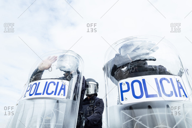 Low angle of anonymous police soldiers in protective uniforms and helmets standing against squad van and defending by riot shields