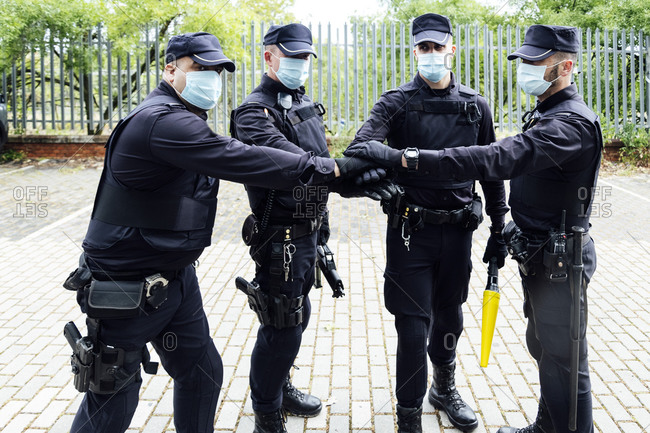 Serious anonymous police officers in protective gears and medical masks armed with guns and batons putting hands together while preparing for operation