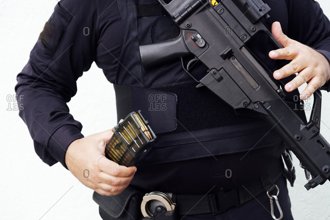 Crop chubby anonymous police officer in dark uniform showing golden bullet made of lead and brass materials while holding firearm in daylight