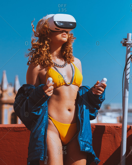 Sensual unrecognizable female traveler in swimwear and VR googles entertaining while watching video with open mouth on roof under blue sky in sunlight