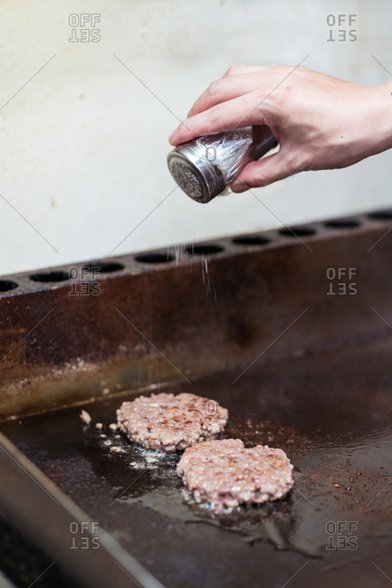 Unrecognizable cook standing at stove in cafe and preparing meat for burgers while adding salt