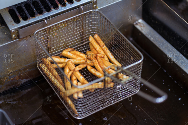 High angle of crispy French fries placed in metal fryer in kitchen of cafe