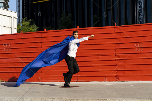 Businessman wearing superhero cape running on pavement