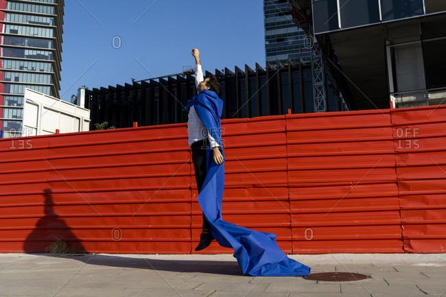 Businessman wearing superhero cape jumping mid-air