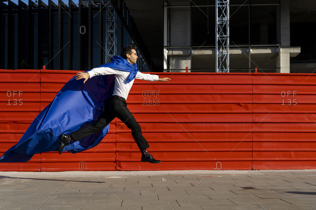 Businessman wearing superhero cape jumping on pavement in the city