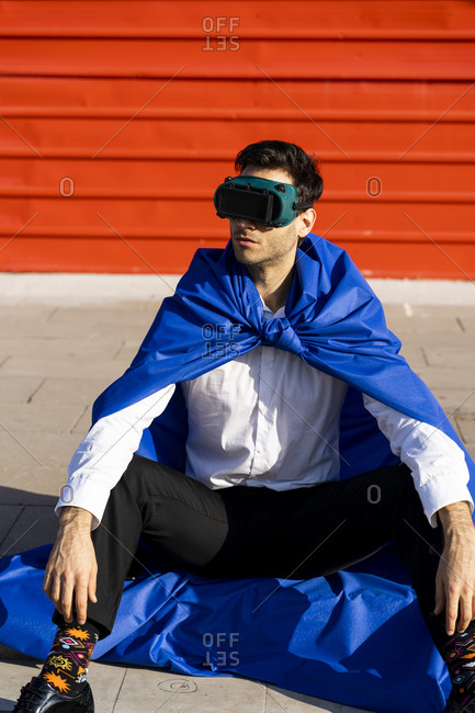 Businessman wearing superhero cape and VR goggles sitting on curb