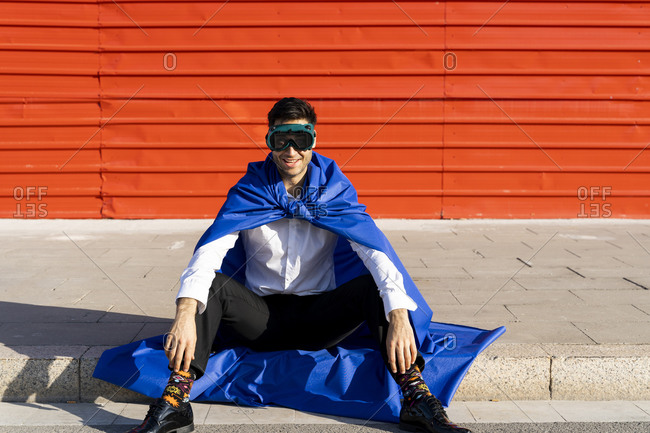 Happy businessman wearing superhero cape and VR goggles sitting on curb