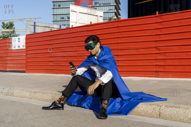 Businessman using smartphone wearing superhero cape and VR goggles sitting on curb