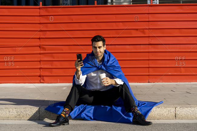 Businessman with smartphone wearing superhero cape sitting on curb
