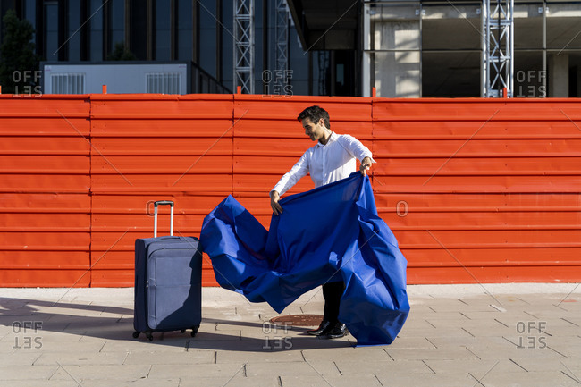 Businessman swinging blue cloth next to wheeled luggage on pavement in the city