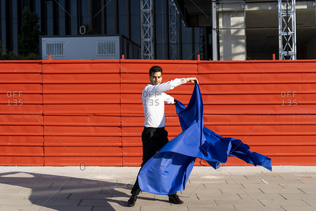 Businessman swinging blue cloth on pavement in the city