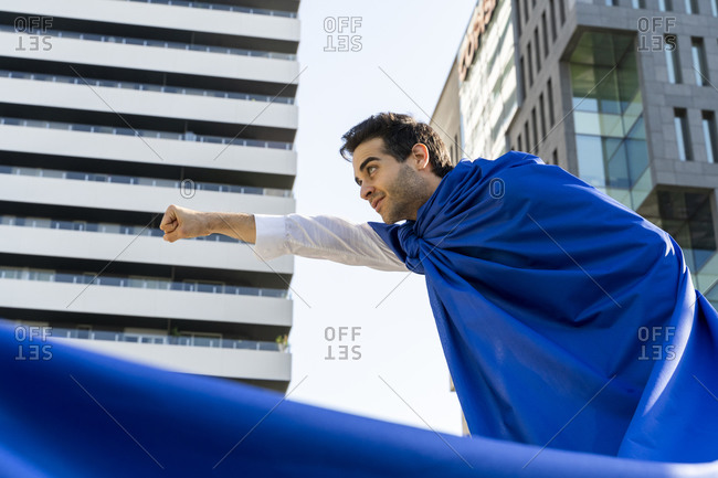 Businessman wearing superhero cape in the city clenching fist